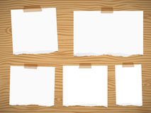 Pieces of torn white blank note paper sticked on brown wooden wall or board.  Stock Image