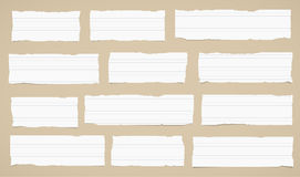 Pieces of torn white lined note paper sticked on brown wall Stock Images