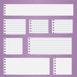 Pieces of torn white lined, squared blank notebook paper sticked on light purple background Stock Images