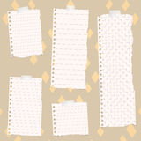 Pieces of torn white lined and squared notebook paper on colorful fabric pattern Stock Images