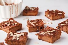 Pieces of vegan pumpkin brownie on white table. Healthy vegan food concept. royalty free stock photos