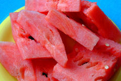 Pieces of watermelon. On the yellow plate with blue background Stock Photos