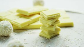 Pieces of white chocolate and coconut candy on a white background