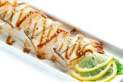 Pieces of white fish with lemon and herbs on a rectangular plate on an isolated white background. Pieces of white fish with lemon and herbs on a rectangular stock photo