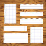 Pieces of white lined, squared notebook paper sheet sticked on brown wooden wall or desk Stock Photos