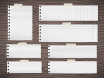 Pieces of white squared note paper sticked on brown wooden wall or desk Stock Photography