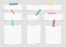Pieces of white torn note, notebook paper sheets with colorful adhesive, sticky tape stuck on grey background Stock Images