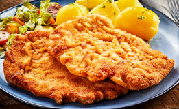 Pieces of Wiener schnitzel with potatoes. Pieces of Wiener golden fried schnitzel with boiled potatoes and salad close-up on grey plate Stock Photo