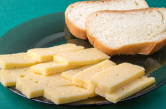 Pieces of yellow hard dry cheese and white bread slices. On a plate on a green background Stock Photos