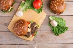 Pieczarkowi hamburgery na nieociosanym drewnianym stole, odgórny widok zdjęcia royalty free