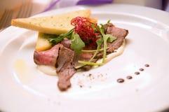 Pieczona wołowina i grzanka z arugula na bielu talerzu Obrazy Royalty Free