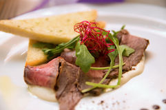 Pieczona wołowina i grzanka z arugula na bielu talerzu Obraz Stock