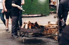 pieczone mięso mężczyzna mienia stalowi jęzory i prażak wzmacniają wieprzowinę o Zdjęcie Stock