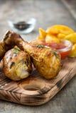 Pieczonego kurczaka drumsticks na tnącej deski i wieśniaka drewnie Obrazy Stock