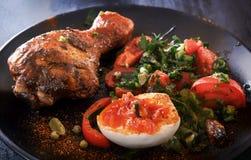 Pieczony kurczak noga w czarnym talerzu z sałatką, jajkiem i kumberlandem pomidorowymi, Zdjęcie Stock