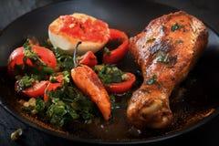 Pieczony kurczak noga w czarnym talerzu z sałatką pieprz, jajko i kumberland pomidorowy i gorący, Obrazy Royalty Free