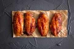 Pieczony kurczak uskrzydla na zmroku - szary tło Fotografia Stock