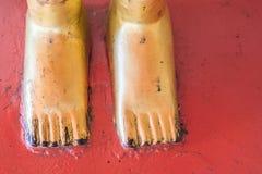 Pied d'or de statue de Bouddha sur le plancher rouge Images stock