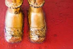 Pied d'or de statue de Bouddha sur le plancher rouge Photographie stock