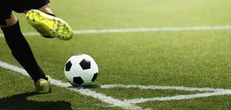 Pied d'un joueur et d'une boule de football d'enfant sur le terrain de football photographie stock