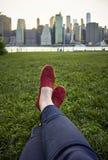 Pied dans des chaussures de toile sur l'herbe verte Photographie stock