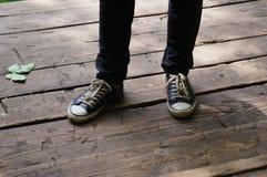 Pied dans des espadrilles se tenant sur le plancher en bois Image libre de droits