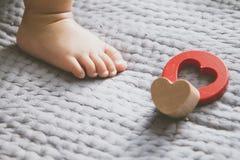 Pied de bébé et jouet rouge sur le lit photos stock