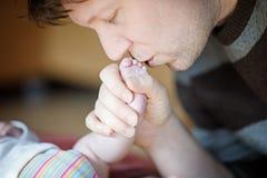 Pied de baiser de père de bébé nouveau-né Images stock