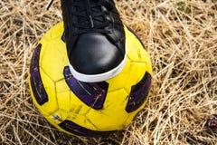 Pied de femme dans les espadrilles et le ballon de football sur un champ sec Image stock
