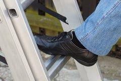 Pied de femme sur l'échelle en aluminium dans le jardin photographie stock libre de droits