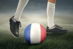 Pied de joueur et de boule de football sur le pré Images stock