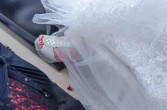 Pied de la jeune mariée dans sandales blanches et un fragment d'une robe de mariage Images libres de droits