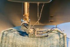 Pied de machine à coudre sur le tissu de jeans Images stock