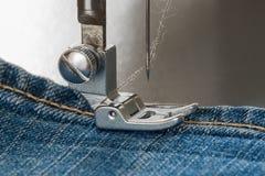 Pied de machine à coudre sur le tissu de jeans Photographie stock