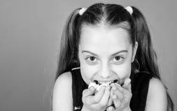 Pied de mouton incorrigible Le visage de sourire de fille tient le fond violet doux de guimauves ? disposition Concept de pied de photos stock