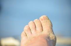 Pied de Womans avec le sable Image stock