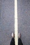 Pied et jambes de Selfie avec la ligne blanche sur la route bétonnée Photo stock
