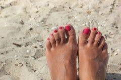 Pied femelle avec une pédicurie sur la plage Photo libre de droits