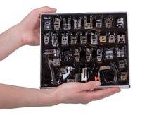 Pied multifonctionnel de presser de kit à la machine à coudre dans des mains de femme d'isolement sur le blanc Photographie stock libre de droits
