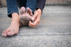 Pied sale d'un homme s'asseyant sur le vieux plancher en béton Photos libres de droits