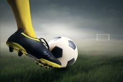 Piede che dà dei calci al pallone da calcio Immagini Stock Libere da Diritti