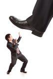 Piede dell'uomo d'affari che fa un passo sull'uomo d'affari molto piccolo Immagini Stock