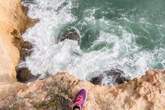 Piede della donna che sta sul bordo della scogliera sopra il mare Immagini Stock
