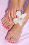 Piede della donna con l'orchidea Fotografia Stock Libera da Diritti