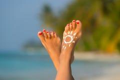 Piede della donna con la crema a forma di Sun del sole nel conce tropicale della spiaggia Fotografia Stock