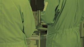 Piede della gamba in un vestito sterile Fotocamera panorama tecnologia di produzione nana del microchip microprocessore atmosfera video d archivio