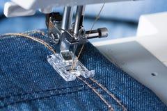 Piede della macchina per cucire sul tessuto dei jeans Fotografie Stock