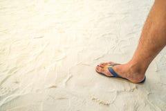 Piede destro dell'uomo con la passeggiata della scarpa sulla sabbia della spiaggia Immagini Stock