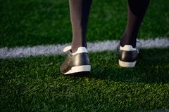 Piede di un calciatore o di un giocatore di football americano su erba verde Fotografia Stock