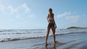 Piede nudo della donna che cammina sulla spiaggia di estate chiuda sulla gamba della giovane donna che cammina lungo l'onda dell' archivi video